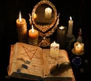 与不可思议书、蜡烛和mirrow的神秘的静物画 免版税库存照片