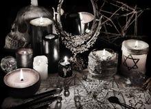与不可思议的镜子、邪魔纸和蜡烛的神秘的静物画在难看的东西葡萄酒样式 库存图片