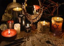 与不可思议的镜子、邪魔纸和蜡烛的神秘的静物画 免版税库存照片