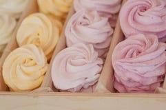 与不同的颜色空气奶油的可口甜饼干蛋白甜饼在箱子的待售,在一家甜商店里面 免版税库存照片