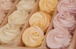 与不同的颜色空气奶油的饼干蛋白甜饼在箱子的待售,在一家甜商店里面 库存图片