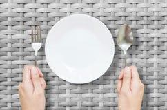 与不锈的叉子的特写镜头白色陶器和匙子在灰色木织法桌上的妇女手上构造了在顶视图的背景 免版税库存图片