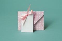 与与一把桃红色弓的空白的白皮书卡片下在绿松石背景包围 免版税库存图片