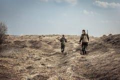 与与猎枪探索乡区的人猎人的狩猎场面在狩猎期期间 免版税库存图片