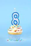 与与被点燃的第的被冰的生日杯形蛋糕8个蜡烛 库存图片