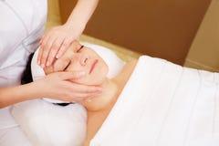 与专业按摩的面部治疗  免版税库存图片