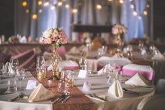 与专属植物布置的婚礼桌为在玫瑰色金子颜色的招待会、婚礼或者事件焦点做准备 免版税库存照片