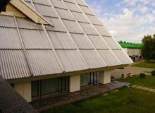 与专栏、全景窗口、倾斜的屋顶和绿草草坪的老俄国旅馆` s门面在入口旁边 图库摄影
