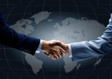 与世界的地图的握手在背景中 免版税库存照片