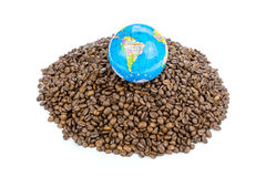 与世界的地球在整个咖啡豆堆  免版税库存图片