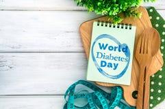 与世界糖尿病天文本的笔记薄在有木头的砧板 免版税图库摄影