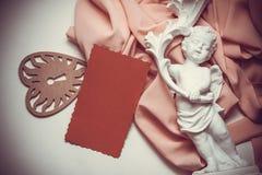 与丘比特和红色明信片的葡萄酒背景与拷贝空间 免版税库存图片