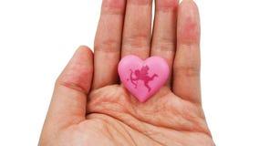 与丘比特的桃红色心脏在白色背景隔绝的妇女的手上 爱和情人节概念 免版税图库摄影