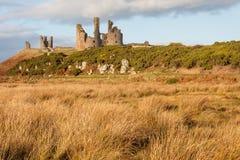 与丛沼泽地的Dunstanburgh城堡在诺森伯兰角 图库摄影