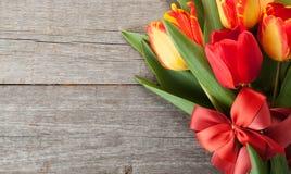 与丝带和弓的新鲜的五颜六色的郁金香花束 免版税库存照片