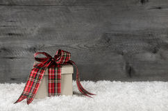 与丝带的一个红色绿色方格的圣诞节礼物在木 库存图片