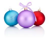 与丝带的三个圣诞节球红色、蓝色和紫色鞠躬 免版税库存图片