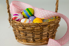 与丝带的各种各样的复活节彩蛋在柳条筐 库存照片