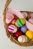 与丝带的各种各样的复活节彩蛋在柳条筐 免版税图库摄影