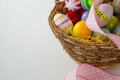 与丝带的各种各样的复活节彩蛋在柳条筐 免版税库存照片