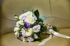 与丝带的婚姻的花束 玫瑰,小苍兰 米黄背景 图库摄影