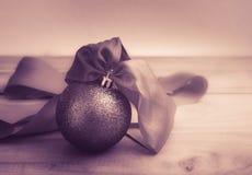 与丝带的抽象紫罗兰色口气圣诞节球在木的桌上 免版税图库摄影