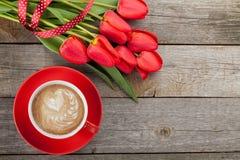 与丝带的新鲜的红色郁金香和有心脏的咖啡杯塑造 免版税图库摄影