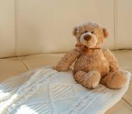 与丝带的玩具熊坐在米黄皮革沙发背景的舒适被编织的白色圣诞节毛线衣 温暖的舒适的冬天 库存图片
