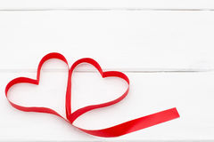 与丝带的红色心脏在白色木背景 库存照片