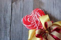 与丝带的红色心脏糖果在老木板背景 华伦泰` s日概念 免版税库存图片