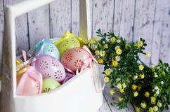 与丝带的色的鞋带复活节彩蛋在白色木篮子鞠躬 库存照片