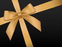 与丝带的金弓 在黑色的发光的假日金缎丝带 库存照片