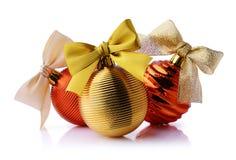 与丝带的金黄和红色圣诞节球鞠躬 免版税库存照片
