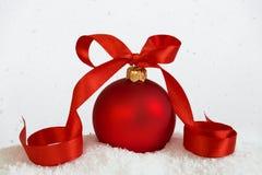 与丝带落的雪的大圣诞节球 免版税库存照片