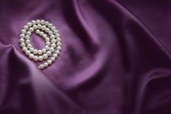 与丝绸和珍珠的典雅的紫色背景 库存图片