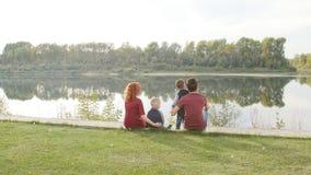 与两个儿子的愉快的年轻家庭在公园走并且休息由河 家庭和关系概念
