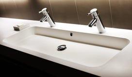与两个光亮的龙头的现代白色水槽,轻拍 库存图片