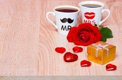 与两个咖啡杯、心脏、礼物和玫瑰色花的背景 免版税库存照片