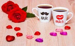与两个咖啡杯、心脏和玫瑰色花的背景 图库摄影