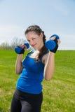 与两个哑铃的健身锻炼 免版税库存照片