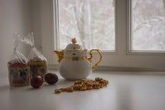 与两个复活节蛋糕、鸡蛋、百吉卷和茶壶的静物画 库存图片