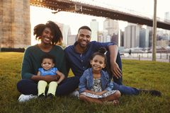 与两个女儿的年轻家庭坐草坪,关闭  库存照片