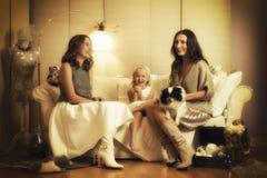 与两个女孩、一个孩子和一条狗的圣诞节photosession在温暖的轻的演播室 图库摄影