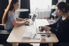 与两个女孩的起始的企业概念现代明亮的办公室内部研究的膝上型计算机和片剂计算机 免版税库存照片