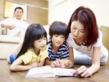 与两个孩子的亚洲母亲阅读书 库存图片