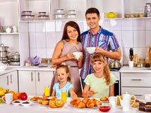 与两个孩子的大家庭食用早餐在厨房 图库摄影