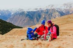 与两个孩子的家庭在风景冬天山旅行 库存照片