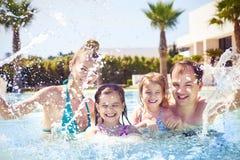 与两个孩子的家庭获得乐趣在游泳池 库存照片