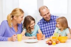 与两个孩子的愉快的家庭与食用早餐 免版税库存图片