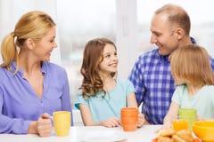 与两个孩子的愉快的家庭与食用早餐 免版税图库摄影